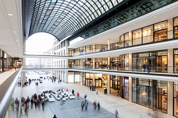 modern shopping mall with stores, cafe and shoppers walking around - shopping mall stock photos and pictures