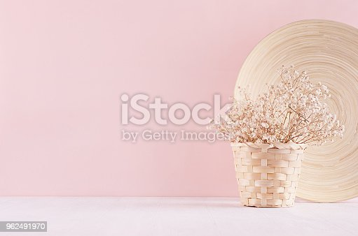 Modern simple art pink home decor with white dried flowers, bamboo dish on soft light white wood table.