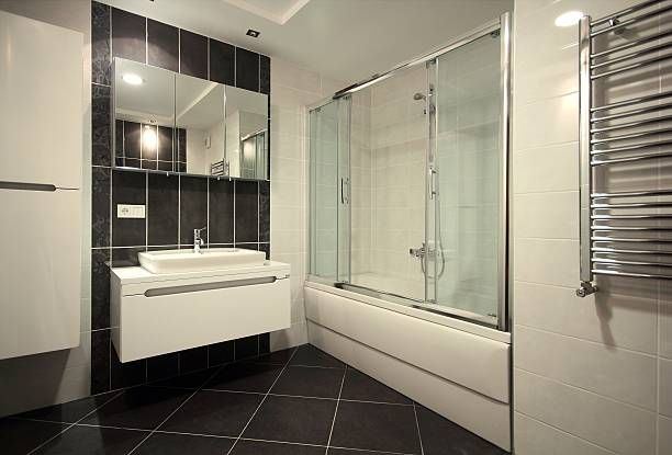 Modern sink and shower in bathroom with black flooring