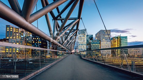 Beautiful twilight over downtown Oslo, the capital city of Norway at Pedestrian Bridge over rails of central railway station. Illuminated modern buildings and skyscapers. Cityscape from elevated walkway in late summer. Oslo, Norway, Scandinavia