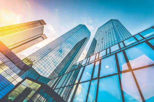 grattacieli moderni nel quartiere degli affari al tramonto con effetto bagliore dell'obiettivo - mercato luogo per il commercio foto e immagini stock