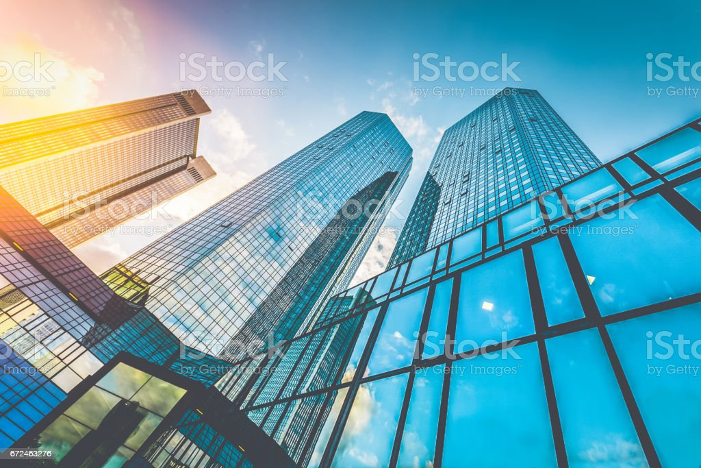Modern skyscrapers in business district at sunset with lens flare effect stock photo
