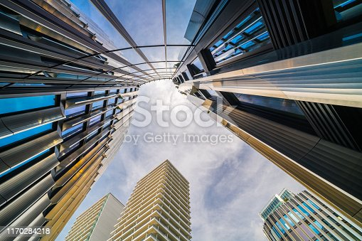 High-rise buildings on blue sky background. White clouds and sunlight. Bottom view. Prague city, capital of Czech Republic
