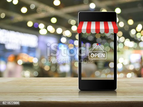 istock Modern smart mobile phone with on line shopping store graphic 621822666