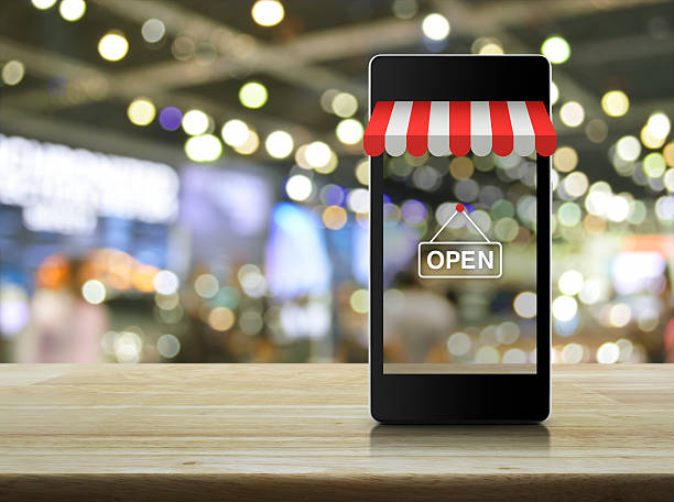 Modern smart mobile phone with on line shopping store graphic Modern smart mobile phone with on line shopping store graphic and open sign on wooden table over blur light and shadow of mall e commerce stock pictures, royalty-free photos & images