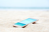 Modern smart phone on the beach with travel photo. Vacation background.