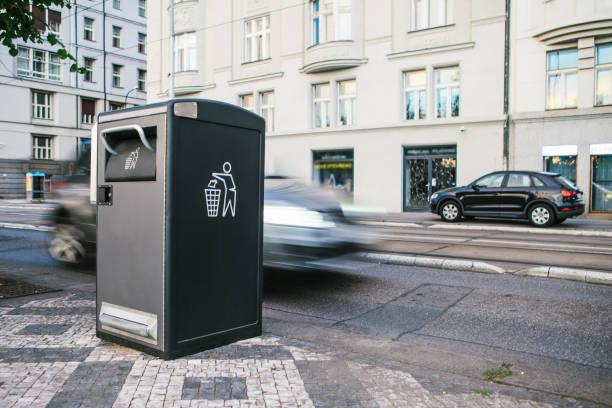 uma moderno inteligente lata de lixo na rua em praga, na república checa. coleta de resíduos na europa para posterior eliminação. ecológica de recolha de resíduos. no fundo, o carro está em movimento. - lixeira - fotografias e filmes do acervo
