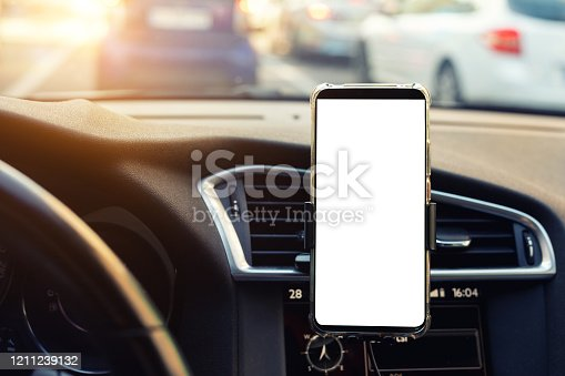 Modern smartphone device gadget mounted on phone holder at car dashboard. Mock-up white screen isolated template. Copyspace for text . Vehicle interior cockpit view. Traffic jam info app.