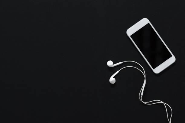 moderno smartphone con la pantalla en blanco y auriculares aislados en negro - foto de stock