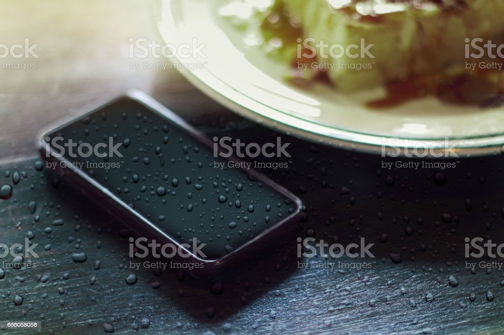 modern smartphone with water drops on food wood table background