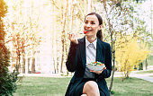Modern smiling business woman in a black suit with a fork eating a vegetable salad outdoors