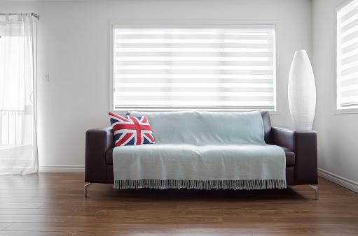 modern sofa in bright living room with zebra blinds stock