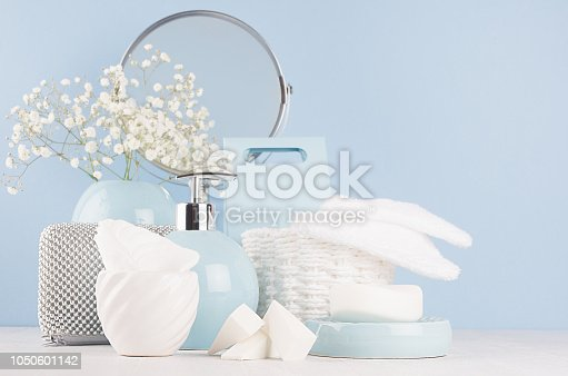 1056636898 istock photo Modern soft light interior for bathroom - pastel blue ceramic bowls, flowers, mirror, silver cosmetic accessories on white wood board and blue wall. 1050601142