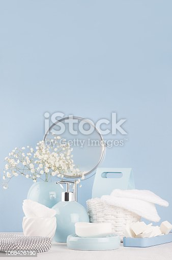1056636898 istock photo Modern soft light interior for bathroom - pastel blue ceramic bowls, flowers, mirror, silver cosmetic accessories on white wood board and blue wall, vertical. 1068426190
