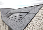 A new set of solar panels which blend in nicely with a black tiled roof.