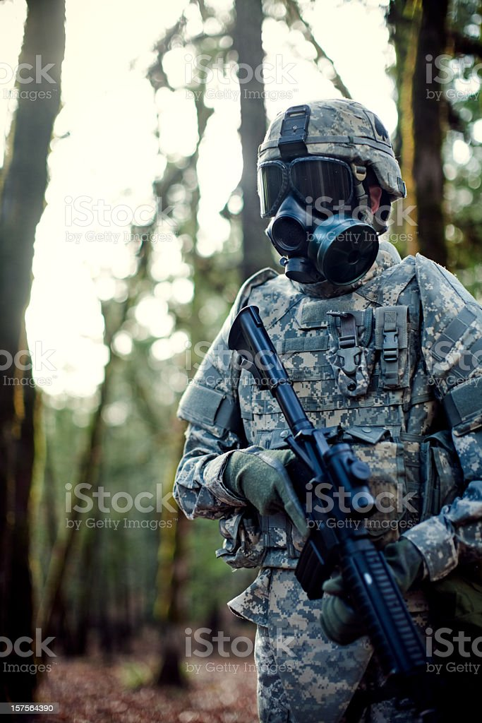 Modern Soldier in Dark Woods with Gun stock photo