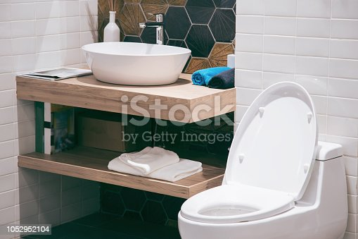 istock Modern spacious bathroom with bright tiles with toilet and sink. Side view 1052952104