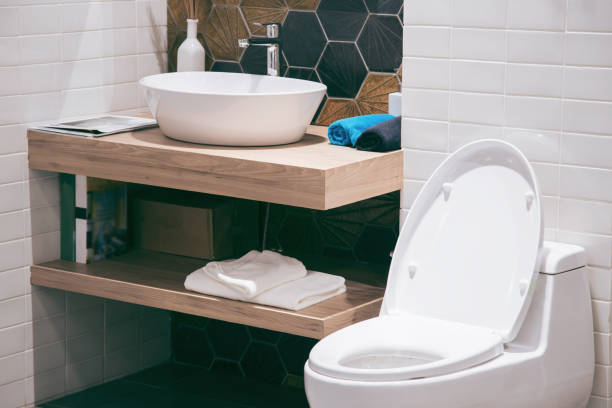 Modern spacious bathroom with bright tiles with toilet and sink. Side view stock photo