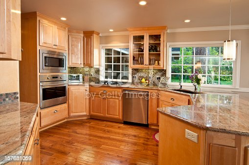 This modern kitchen gives a wide view showing the wood floor and cabinets.
