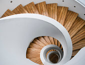Top-view photo of a spiral staircase. Forms a nautilus-shaped abstract pattern.