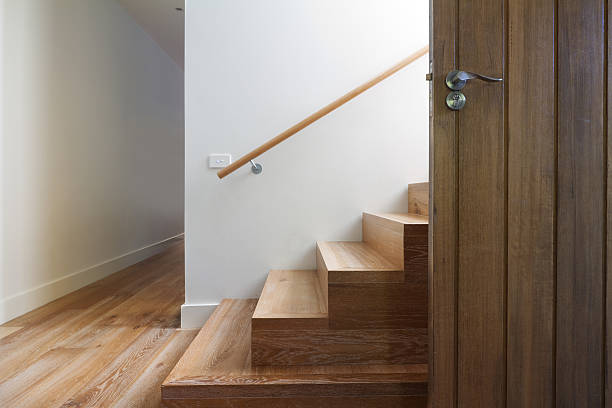 Modern staircase of oak wood beside front door horizontal stock photo