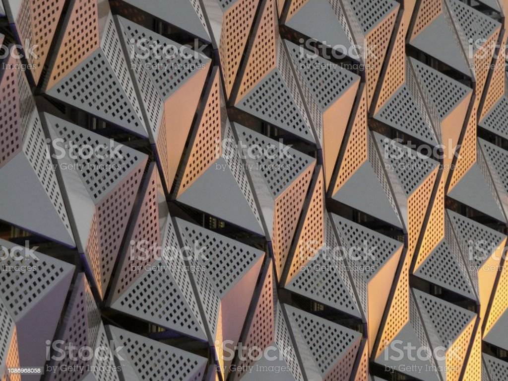 modern steel angular geometric cladding with colour tones and perforated patterned design stock photo