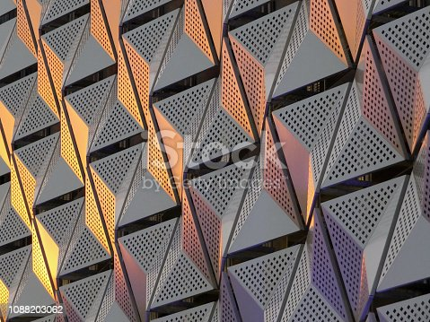 modern steel cladding with angular geometric patterns  and square holes in a shiny metallic finish with colored reflection on the wall of a car park in leeds university district