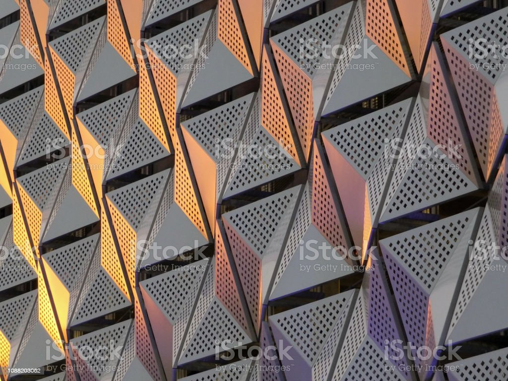 modern steel cladding with angular geometric patterns  and square holes in a shiny metallic finish with colored reflection on the wall of a car park in leeds stock photo