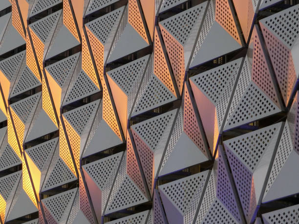 modern steel cladding with angular geometric patterns  and square holes in a shiny metallic finish with colored reflection on the wall of a car park in leeds - abstract architecture стоковые фото и изображения