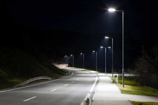lampadaires modernes avec la technologie led la nuit, route moderne vide - éclairage public photos et images de collection