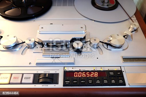 istock Modern studio stereo tape recorder with magnetic tape front view closeup 828944464