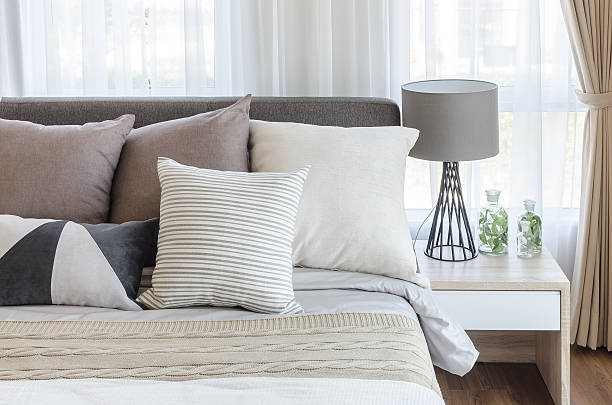 modern style bedroom with pillows on bed modern style bedroom with pillows on bed and modern grey lamp on side table at home cushion stock pictures, royalty-free photos & images