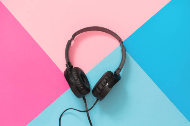 Modern style black headphones on pink blue background. Modern style black headphones on the pink blue background. Top view. mp3 player stock pictures, royalty-free photos & images