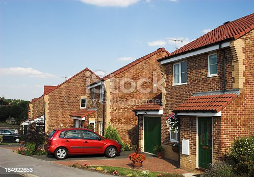 istock Modern suburban family houses with car on driveway 184922653
