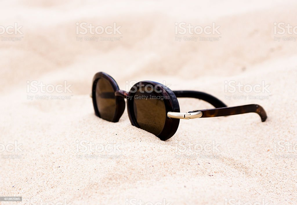 Modern Sunglasses laying in the sand with copy space royalty-free stock photo