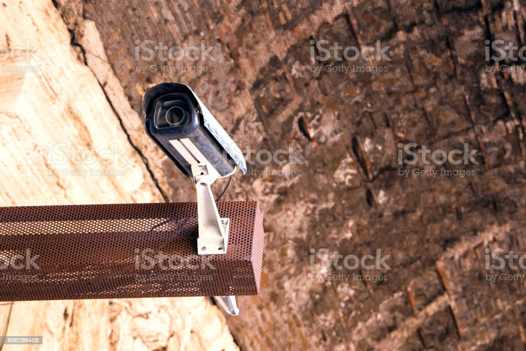 A modern surveillance camera in an antique building stock photo
