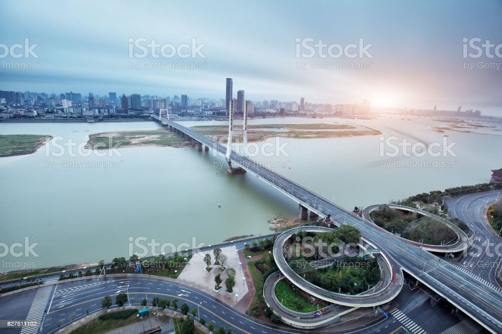 modern suspension bridge over tranquil river and cityscape of modern city stock photo