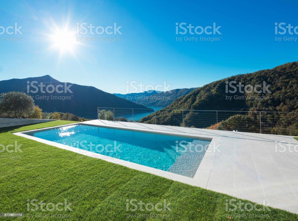 Modernes Schwimmbad mit Blick auf See und Tal – Foto