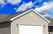 Tan sided modern home with garage door.  Roofing, Blue Sky and clouds in the background. No people.