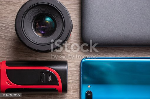 1134879628 istock photo Modern technology flat lay, laptop, camera lens, vaping device and blue smartphone laid out on a table. Perfect simmetry , smartphone reflecting light 1207597277
