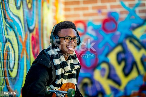 A boy of African descent is sitting in front of a wall with graffiti on it. He is wearing a trendy jacket and scarf. He is smiling while holding a skateboard and listening to music with headphones.