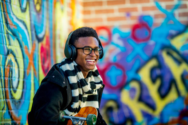 Modern Teenage Boy A boy of African descent is sitting in front of a wall with graffiti on it. He is wearing a trendy jacket and scarf. He is smiling while holding a skateboard and listening to music with headphones. generation z stock pictures, royalty-free photos & images
