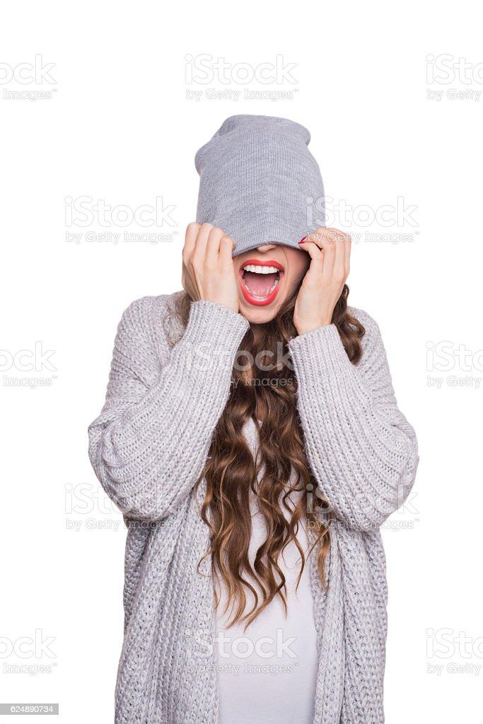 Modern teenage girl in  beanie hat and gray sweater Screaming stock photo