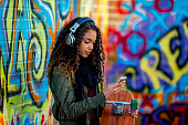A girl of African descent is in front of a wall with graffiti on it. She is wearing trendy clothing. She is sending a message on her smartphone while holding her skateboard.