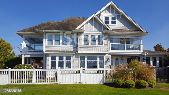 Crescent Beach,Surrey,British Columbia,Canada- September 26,2018: Exterior Front view of wooden board siding  home. Lots of Sash windows. Retro style. White Decorative fence in front. No people. Clear blue sky.