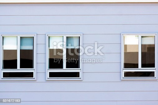 Closeup tree windows on cladding wall of the house, full frame horizontal composition with copy space