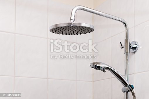 Modern tiles tiled bathroom with shower heads closeup in luxury house room and isolated clean object