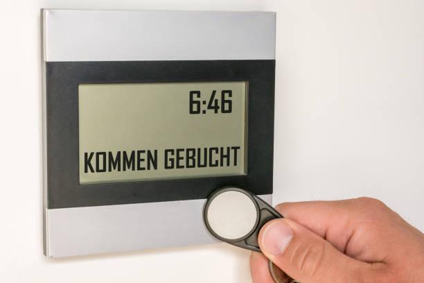 ドイツ語のテキストを持つチップによって時間の記録と現代の時間時計は、「予約来る」 - 出勤 ストックフォトと画像