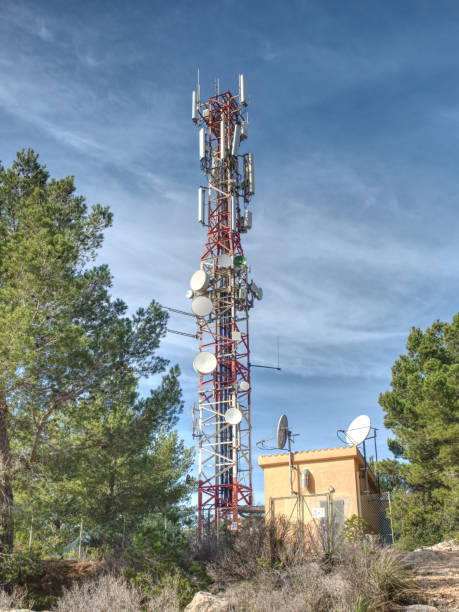 Modern tower with huge complex of telecommunication antennas on old bricks house hidden in pine trees.  Mountain trail over Pintal Vermell peak, Mallorka island, Spanish  Balears islands. stock photo