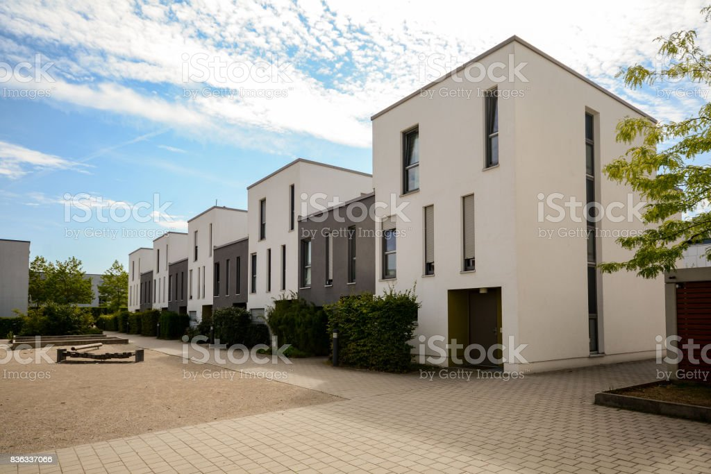 Modern townhouses in a residential area, new apartment buildings with green outdoor facilities in the city stock photo